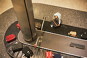 Airline passengers grabs his suitcase from the carousel in the baggage reclaim hall in the arrivals of Heathrow Airport's T5