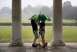 © Licensed to London News Pictures. 25/07/2021. London, UK. Members of the public attempt to collapse an umbrella as they shelter with their dogs during a thunderstorm in Greenwich Park. An amber weather warning for thunderstorms is in place in parts of London and the South East . Photo credit: George Cracknell Wright/LNP