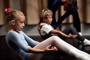 Royal Ballet School Copenhagen. Children taking dance classes do exercises at the beginning of a class. Denmark.