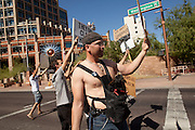 "22 OCTOBER 2011 - PHOENIX, AZ:    An Occupy Phoenix protester crosses a street in downtown on his way to the Occupy Phoenix protest Saturday. The demonstrations at Occupy Phoenix, AZ, entered their second week Saturday. About 50 people are staying in Cesar Chavez Plaza, in the heart of downtown. The crowd grows in the evening and on weekends. Protesters have coordinated their actions with police and have gotten permission from the city to set up shade shelters and sleep in the park, but without tents or sleeping bags, which is considered ""urban camping,"" instead protesters are sleeping on the sidewalk. PHOTO BY JACK KURTZ"