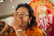 """29 SEPTEMBER 2012 - NAKORN NAYOK, THAILAND:  A woman blows a conch horn during observances of Ganesh Ustav at Wat Utthayan Ganesh, a temple dedicated to Ganesh in Nakorn Nayok, about three hours from Bangkok. Many Thai Buddhists incorporate Hindu elements, including worship of Ganesh into their spiritual life. Ganesha Chaturthi also known as Vinayaka Chaturthi, is the Hindu festival celebrated on the day of the re-birth of Lord Ganesha, the son of Shiva and Parvati. The festival, also known as Ganeshotsav (""""festival of Ganesha"""") is observed in the Hindu calendar month of Bhaadrapada, starting on the the fourth day of the waxing moon. The festival lasts for 10 days, ending on the fourteenth day of the waxing moon. Outside India, it is celebrated widely in Nepal and by Hindus in the United States, Canada, Mauritius, Singapore, Thailand, Cambodia, Burma , Fiji and Trinidad & Tobago.     PHOTO BY JACK KURTZ"""