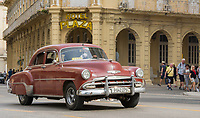 Havana, Cuba - A taxi passes in front of Hotel Plaza near Parque Central. Classic American cars from the 1950s, imported before the U.S. embargo, are commonly used as taxis in Havana.