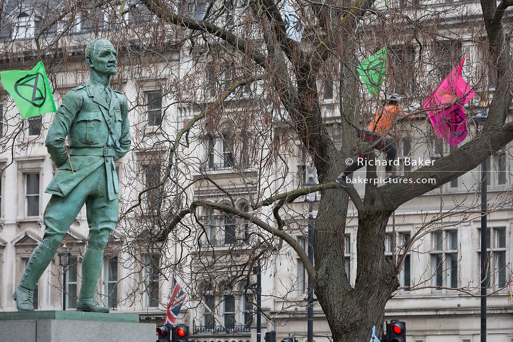 The statue of Field Marshal Jan Christiaan Smuts, the prominent South African and British Commonwealth statesman, military leader and philosopher and a climate change protester during the week-long action by climate change activists with Extinction Rebellion's campaign to block road junctions and bridges around the capital, on 23rd April 2019, in London England.