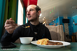 Alessandro Ciceri, known for his cold weather riding and as Wizz on social media (@wizz_inwiaggio), after riding 6,200 mile (10,000 km) from his home in Italy in the middle of winter and after racing on the mile long ice track. Here he is having some lunch just before leaving to ride another 3,100 miles (5,000 Km) through Siberia in winter to Vladivostok as he says goodbye to Lake Baikal after the Baikal Mile Ice Speed Festival. Maksimiha, Siberia, Russia. Monday, March 2, 2020. Photography ©2020 Michael Lichter.