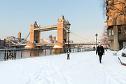 A woman wearing a bobble hat walks on a blanket of snow in front of Tower Bridge in London, England on February 28th, 2018. Freezing weather conditions dubbed the Beast from the East have brought snow and sub-zero temperatures to the UK.