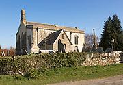 Building exterior historic church of Saint John, Inglesham, Wiltshire, England, UK 13th century building with 15th century churchyard cross
