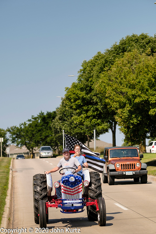 """08 AUGUST 2020 - WEST DES MOINES, IOWA: GARY LEFFLER, from West Des Moines, drives a red, white, and blue tractor down Mills Civic Parkway during a rally to support law enforcement in West Des Moines. About 100 people gathered at the West Des Moines Law Enforcement Center to rally in support of law enforcement. The rally was organized by """"Uplifting Our Police,"""" a local organization that supports law enforcement. They rallied at Des Moines Police headquarters in July. They are planning similar rallies at police stations in the Des Moines metropolitan area.     PHOTO BY JACK KURTZ"""