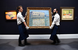 Gallery assistants adjust Le Palais Ducal by Claude Monet, during a photo call for Sotheby's Impressionist, Modern Art and Surrealist Art sales, in London.