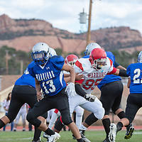 Pine Hill nose tackle Keagan Edison (95), bull rushes the defensive line to bring down Warriors running back Karlton Holyan (21) behind the line of scrimmage, in Navajo on Saturday.