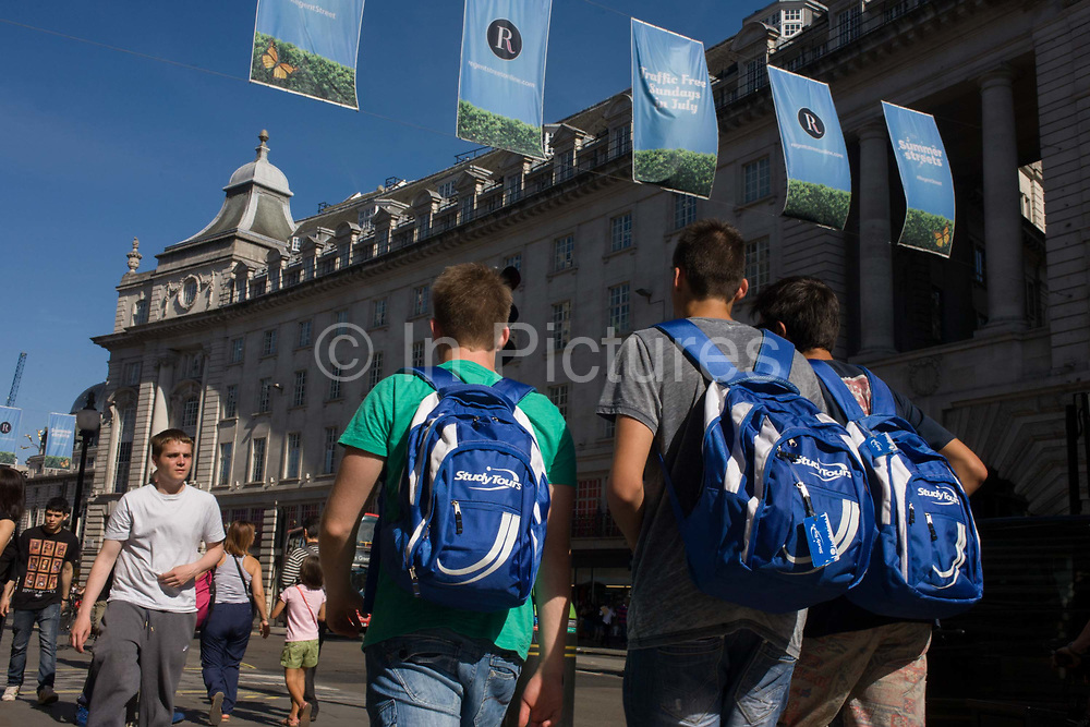 Three young tourists boys carry identical tour rucksacks beneath blue banners across Regent Street, central London. From a low angle we look up to the lads making their way beneath the banners that hang across one of the capital's bust shopping streets. Their matching blue packs have perhaps been given to them by Study Tours, an organisation offering cheap student travel, guided student tours, weekend tours and day trips.