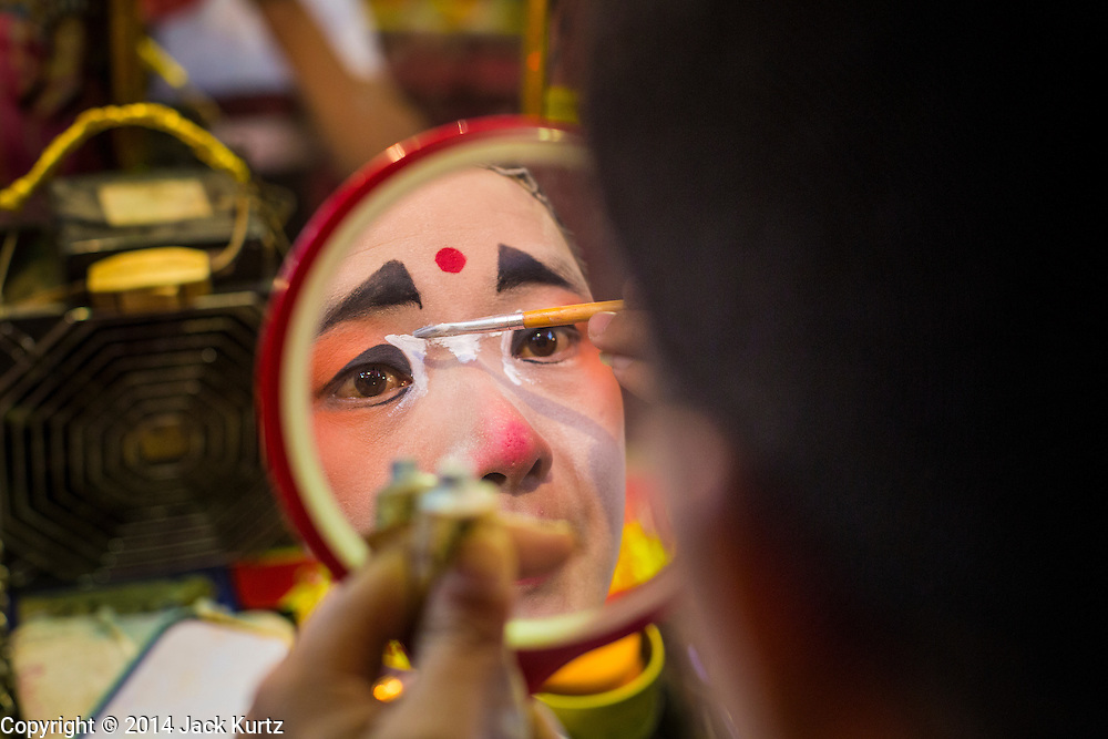 """28 JANUARY 2014 - BANGKOK, THAILAND: A performer with the Tear Kia Ee Lye Heng opera troupe puts on her makeup before a show. They were performing for a business in the Min Buri district of Bangkok for the Lunar New Year, which this year is Jan 31. Chinese opera was once very popular in Thailand, where it is called """"Ngiew."""" It is usually performed in the Teochew language. Millions of Teochew speaking Chinese emigrated to Thailand (then Siam) in the 18th and 19th centuries and brought their cultural practices with them. Recently the popularity of ngiew has faded as people turn to performances of opera on DVD or movies. There are still as many 30 Chinese opera troupes left in Bangkok and its environs. They are especially busy during Chinese New Year when they travel from Chinese temple to Chinese temple performing on stages they put up in streets near the temple, sometimes sleeping on hammocks they sling under their stage. They are also frequently hired by Chinese owned businesses to perform as a form of merit making.    PHOTO BY JACK KURTZ"""