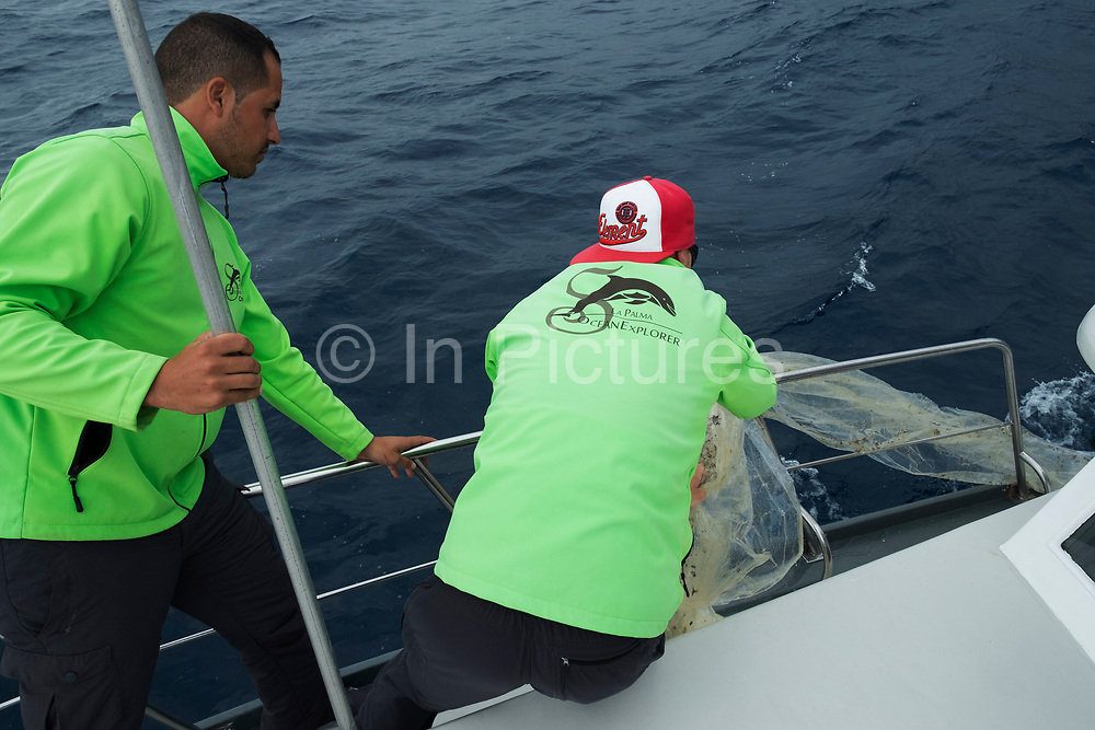 Plastic in the sea is collected by the crew of a whale spotting boat out at sea on the Atlantic Ocean looking towards the volcanic coastline near Tazacorte in La Palma, Canary Islands, Spain. La Palma, also San Miguel de La Palma, is the most north-westerly Canary Island in Spain. La Palma has an area of 706km2 making it the fifth largest of the seven main Canary Islands.