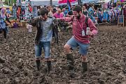 People take a short cut through the mud as it begins to dry - The 2016 Glastonbury Festival, Worthy Farm, Glastonbury.