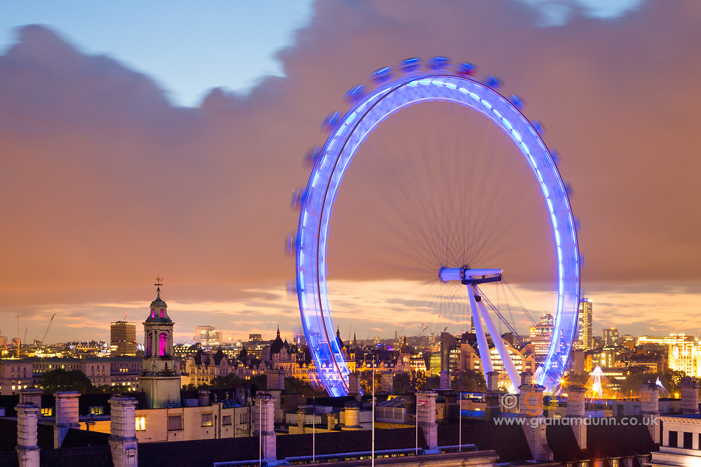 The London Eye at dusk, looking north-west across the rooftops of central London. Taken from an elevated viewpoint near Westminster Bridge. England, UK.