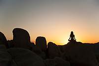 Yoga woman silhouette in the desert sunset.