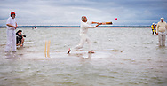 Action during the annual Bramble Bank cricket match in the middle of the sea. The eccentric game involves members of the Royal Southern Yacht Club in Hamble playing against the Island Sailing Club from Cowes on the Brambles, a patch of sand in the Solent, only visible for a few minutes on the spring tide. The teams take turns in winning. This year the Royal Southern team won and hosted dinner at their club house.<br /> Picture date Monday 31st August, 2015.<br /> Picture by Christopher Ison. Contact +447544 044177 chris@christopherison.com