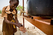 Girl in a school uniform washing hands after using a latrine.Northern Ghana, Wednesday November 12, 2008.