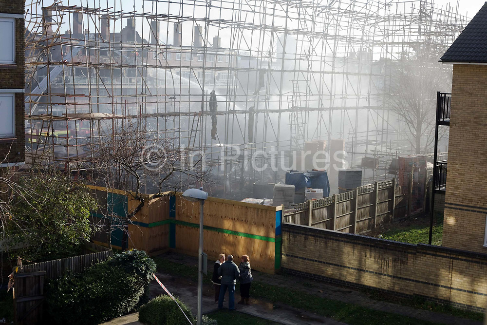 A group of local residents have been allowed past cordons and return to see their devastated estate after an inner-city estate fire in south London. About 310 people were forced to leave their homes after the fire engulfed a wooden structure under construction in scaffolding at Sumner Road and Garrisbrooke Estate, Peckham, London at about 0430 AM. It spread to two blocks of maisonettes and a destroyed a pub. More than 150 firefighters tackled this unusually large and ferocious fire which injured ten people, including two police officers who received hospital treatment for minor injuries.