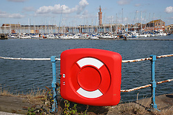 Lifebuoy in front of of former dock at Grimsby now converted to a Marina; with Grimsby Dock Tower in background