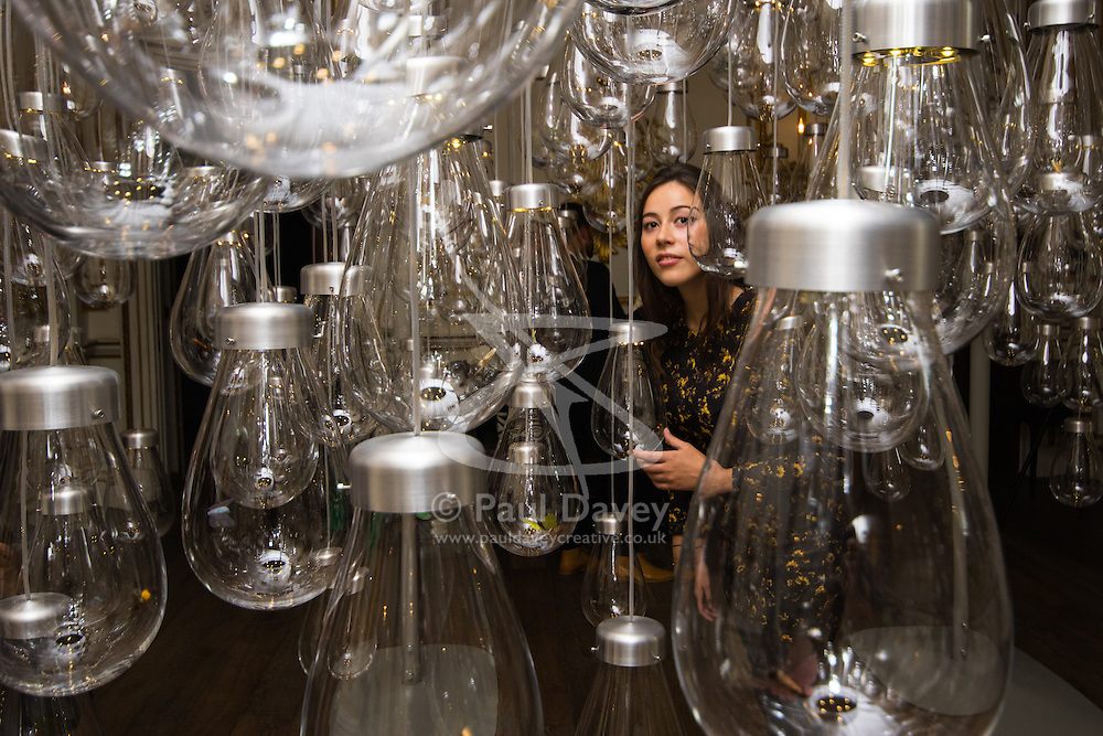 London, September 18th 2015. A woman interacts with Curiosity Cloud by mischer'traxler for Perrier-Jouet. The installation comprises 250 mouth-blown glass globes hang from the ceiling. Each bulb contains a single, hand-made insect. <br /> From a distance the insects are calm but as visitors approach, they come to life, fluttering and trilling as they batter the glass that contains them. The Victoria and Albert museum celebrates the London Design Festival which runs from 19 – 27 September, with a collection of conceptual installation artworks.