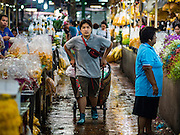 """11 AUGUST 2016 - BANGKOK, THAILAND: A porter pulls his hand truck through the market in Pak Khlong Talat. Pak Khlong Talat (literally """"the market at the mouth of the canal"""") is the best known flower market in Thailand. It is the largest flower market in Bangkok. Most of the shop owners in the market sell wholesale to florist shops in Bangkok or to vendors who sell flower garlands, lotus buds and other floral supplies at the entrances to temples throughout Bangkok. There is also a fruit and produce market which specializes in fresh vegetables and fruit on the site. It is one of Bangkok's busiest markets and has become a popular tourist attraction.             PHOTO BY JACK KURTZ"""