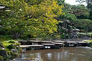 The Flying Wild Geese Bridge (Gankobashi) over a stream and a stone lantern in the Kenrokuen Garden, Kanazawa, Japan