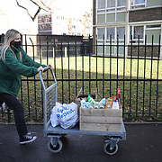 Workers and volunteers at Hackney Foodbank receive and organize food donations, 15th of December 2021, Hackney, East London, United Kingdom. Food donated to the food bank is taken from a car to the ware house. The Hackney Foodbank is part of a nationwide network of foodbanks, supported by The Trussell Trust, working to combat poverty and hunger across the UK. The food bank gives out three days emergency food supplies to families and individual who go hungry in the borrough. The food is all donated by individuals and the food donated is held in a small ware house where it is  sorted and packed for distribution.  More people than ever in Britain have turned to the food bank for help and in Hackney the need has gone up with 350% over the past two years.