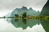 A barefoot man walks across the Li River near Yangshuo, China.