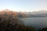 On the left is Nariz del Indio, Indian Nose named because of a fancied resemblance to an Indian's brow, nose lips and chin. Across Lago Atitlan is the town of San Pablo. Santa Clara la Laguna. Republic of Guatemala. 05Mar14