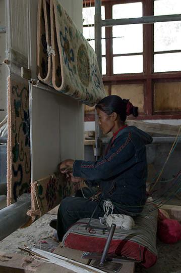 Lady weaving rugs made of yak wool in factory. Tibet. Asia.