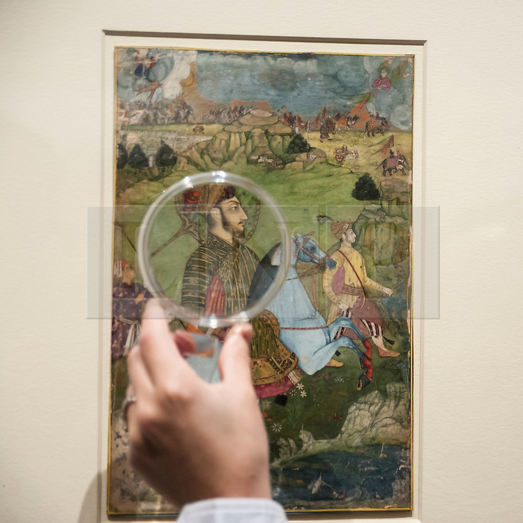 """© Licensed to London News Pictures. 02/10/2015. London, UK. A visitor uses a magnifying glass to view """"A prince holding a falcon and galloping through a rocky landscape, Deccan, Golconda"""" (est. £60k - 80k), a highlight from the Sven Gahlin Collection of 157 finely painted Indian miniature paintings at the preview of Indian and Islamic Art Week at Sotheby's which runs from 2 to 7 October.   Photo credit : Stephen Chung/LNP"""