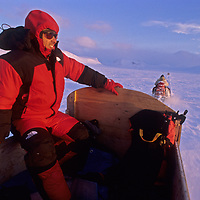 Greg Child rides in a komatik sled pulled by a snowmobile, en route to a climbing expedition on Great Sail Peak north of the Arctic Circle on Baffin Island, Nunavut, Canada.