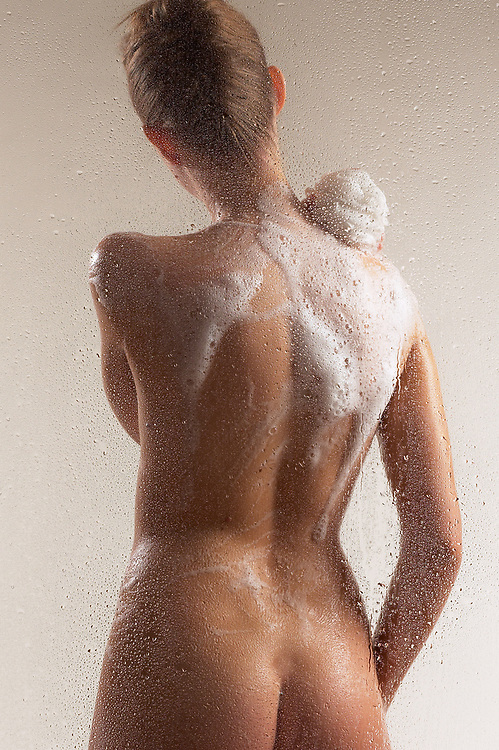 Back view of woman soaping in shower with gray background