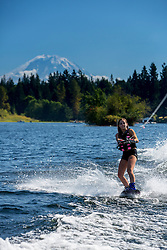 United States, Washington, Lake Sawyer, teen girl wakeboarding in front of Mt. Rainier.  MR