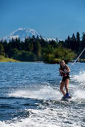 United States, Washington, Lake Sawyer, teen girl wakeboarding in front of Mt. Rainier.  MR