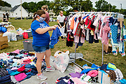 """19 JULY 2020 - DES MOINES, IOWA: Volunteer HAYLEY PRATT sorts donated clothing before """"A Celebration of Black Motherhood"""" in Des Moines Sunday. The event was organized by the Supply Hive and Black Lives Matter. Items were donated by members of the community and redistributed to at risk families. They distributed diapers, sanitary products, clothes, books, and toys. They had enough material to help 200 families.       PHOTO BY JACK KURTZ"""