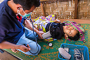 03 MARCH 2104 - MAE KASA, TAK, THAILAND:  A medic takes the vitals of a young man with tuberculosis at the Sanatorium Center for Border Communities in Mae Kasa, about 30 minutes north of Mae Sot, Thailand. The Sanatorium provides treatment and housing for people with tuberculosis in an isolated setting for about 68 patients, all Burmese. The clinic is operated by the Shoklo Malaria Research Unit and works with several other NGOs that assist Burmese people in Thailand. Reforms in Myanmar have alllowed NGOs to operate in Myanmar, as a result many NGOs are shifting resources to operations in Myanmar, leaving Burmese migrants and refugees in Thailand vulnerable. Funding cuts could jeopardize programs at the clinic. TB is a serious health challenge in Burma, which has one of the highest rates of TB in the world. The TB rate in Thailand is ¼ to ⅕ the rate in Burma.        PHOTO BY JACK KURTZ