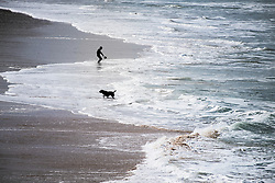 A boy and a dog seen in silhouette and from a distance on Fistral Beach in Newquay, Cornwall.