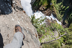 Low section of man climbing rock face via ferrata towards Stuibenfall Waterfall, Otztal, Tyrol, Austria
