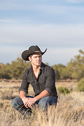 cowboy squatting in a field