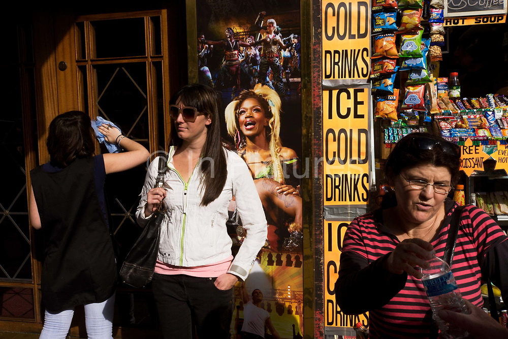 Street scene people outside the Dominion Theatre where the 'We will Rock You' musical is staged, London. A woman polishes the glass doors of the theatre minutes before a matinee performance, a young girl awaits a friend in front of a poster of characters from the production. A women to the right accepts a bottle of mineral water from an unseen partner. A vertical banner from a kiosk selling ice cold drinks and various snacks is behind.