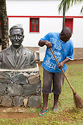 A man sweeps in from of a statue of Antonio Jorge de Silva, a former respected Colonial Governor, Principe, Sao Tome and Principe. Sao Tome and Principe, are two islands of volcanic origin lying off the coast of Africa. Settled by Portuguese convicts in the late 1400s and a centre for slaving, their independence movement culminated in a peaceful transition to self government from Portugal in 1975.