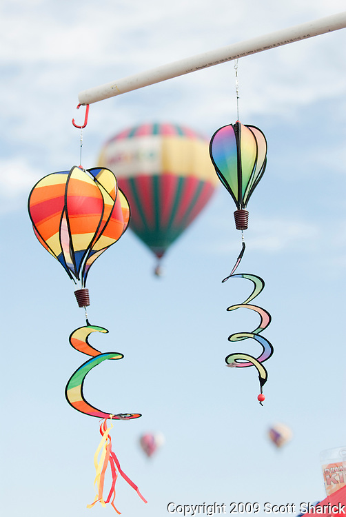 Two toy hot air balloons for sale with a real hot air balloon in the air behind them.