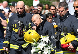 Firefighters look at the floral tributes left by the Latymer Community Centre before a minute's silence near to Grenfell Tower in west London after a fire engulfed the 24-storey building on Wednesday morning.