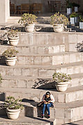 A woman eats her lunch sitting on giant stone blocks along the Santa Lucia Riverwalk at the Museum of the Northeast or Museo del Noreste adjacent to the Macroplaza Grand Plaza in the Barrio Antiguo neighborhood of Monterrey, Nuevo Leon, Mexico.