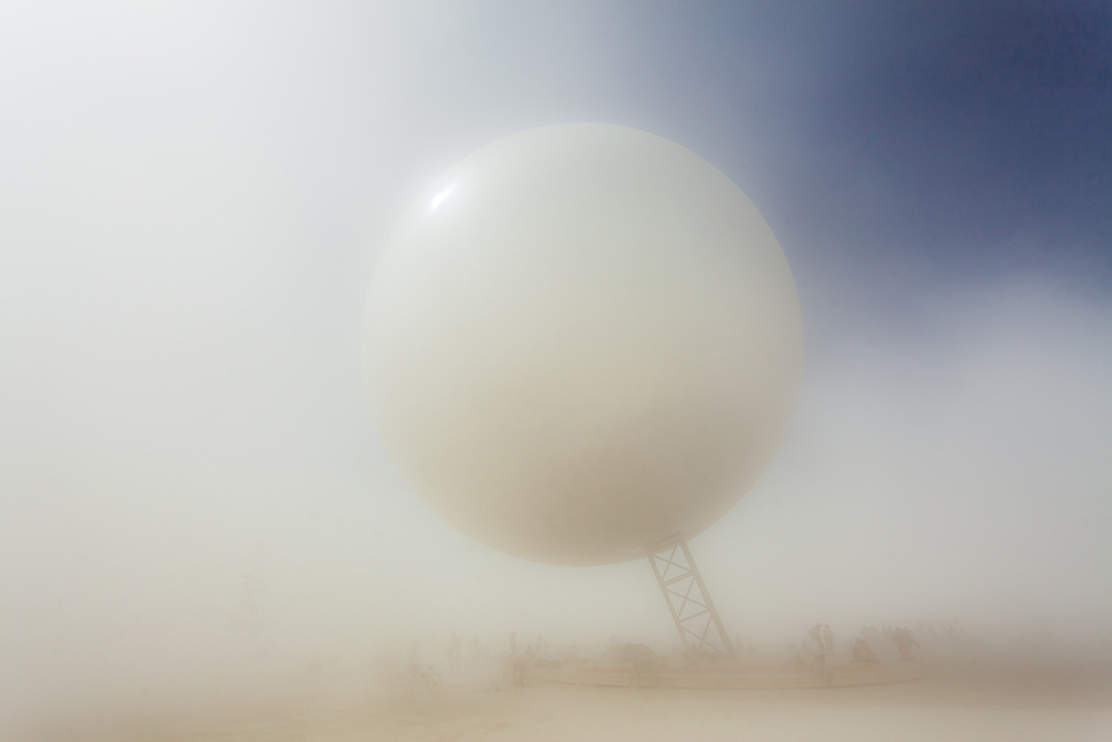 The ORB by: Bjarke Ingels, Jakob Lange, and I, Orbot from: Valby, Copenhagen, Denmark year: 2018<br /> <br /> Inspired by NASA's Project Echo, the ORB is an inflatable structure to levitate above the playa. The reflective skin will mirror the full layout of BRC from the ground, allowing for easier navigation & making visible the burner's immersion in the community space.