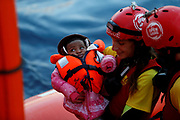 A crew member of MV Open Arms, the search and rescue ship of Proactiva Open Arms, carries a migrant baby before passing it to crew members of MV Aquarius, a search and rescue ship run in partnership between SOS Mediterranee and Medecins Sans Frontieres, during a mid-sea transfer of migrants in the central Mediterranean off the coast of Libya, December 16, 2017.    REUTERS/Darrin Zammit Lupi     TPX IMAGES OF THE DAY - RC11DAEB6860