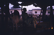 A Husa man listens to the radio at dusk Camel and sheep market, Kano..The implementation of Islamic Sharia Law across the twelve northern states of Nigeria, centres upon Kano, the largest Muslim Husa city, under the feudal, political and economic rule of the Emir of Kano. Islamic Sharia Law is enforced by official state apparatus including military and police, Islamic schools and education, plus various volunteer Militia groups supported financially and politically by the Emir and other business and political bodies. Fanatical Islamic Sharia religious traditions  are enforced by the Hispah Sharia police. Deliquancy is controlled by the Vigilantes volunteer Militia. Activities such as Animist Pagan Voodoo ceremonies, playing music, drinking and gambling, normally outlawed under Sharia law exist as many parts of the rural and urban areas are controlled by local Mafia, ghetto gangs and rural hunters. The fight for control is never ending between the Emir, government forces, the Mafia and independent militias and gangs. This is fueled by rising petrol costs, and that 70% of the population live below the poverty line. Kano, Kano State, Northern Nigeria, Africa