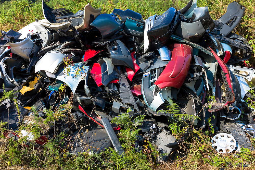 Broken car body parts for metal recycling at Renault motor dealers in Asturias, Northern Spain