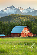 Red barn beneathe the Como Peaks in the Bitterroot Valley, Montana.
